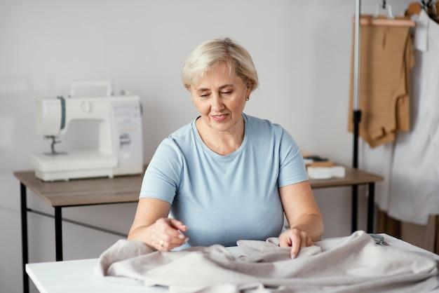Alfaiate sorridente feminina no estúdio com tecido