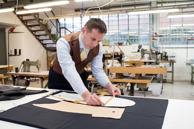 Alfaiate, trabalhando com padrões de papel na jaqueta nova
