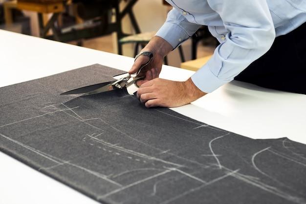 Alfaiate, trabalhando em sua loja de corte de tecido