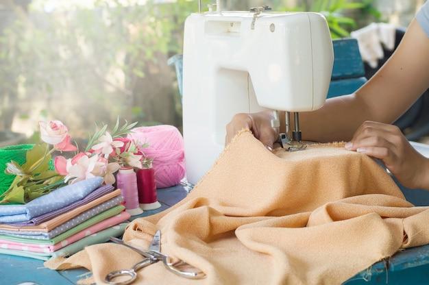 Alfaiate trabalhando em uma máquina de costura com tecido laranja