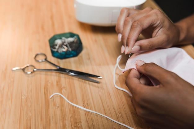 Alfaiate usando uma agulha para fazer uma máscara de tecido