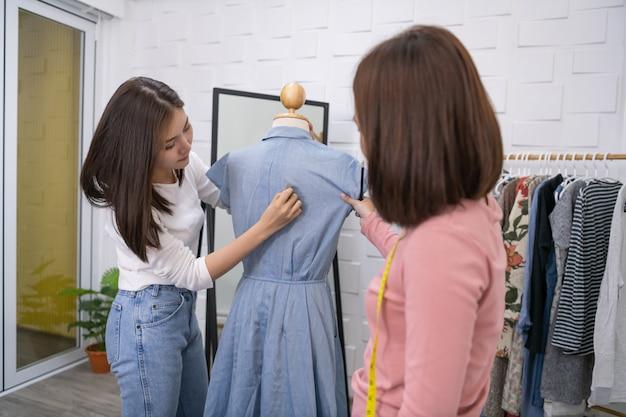 Alfaiates estão ajudando a trabalhar seriamente. jovem é projetar roupas no quarto.