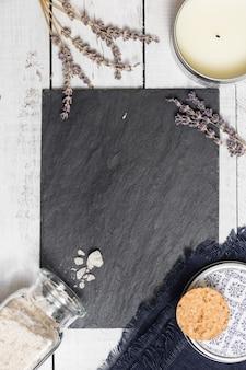Alfazema na placa preta da grafite em cima da tabela de madeira rústica branca.