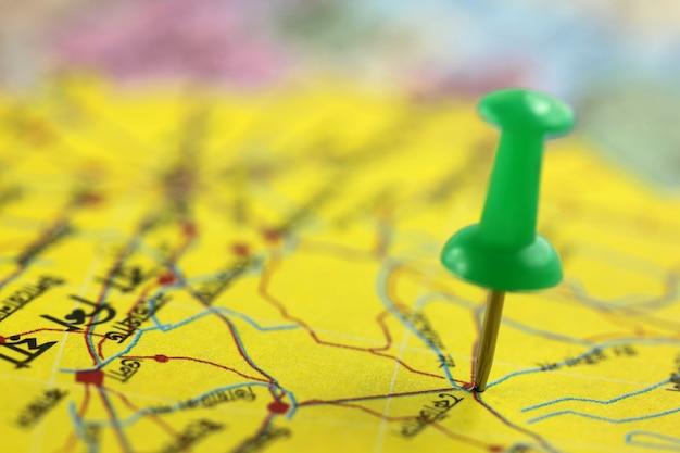 Alfinete apontando para um lugar em um mapa de papel
