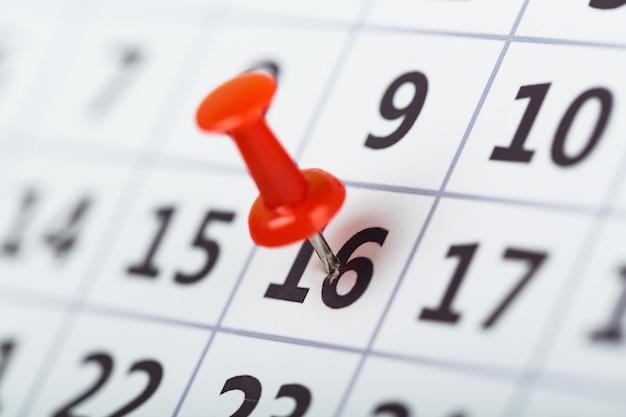 Alfinete bordado em calendário no dia 16 com foco seletivo