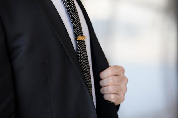 Alfinete dourado na gravata de um homem de terno.