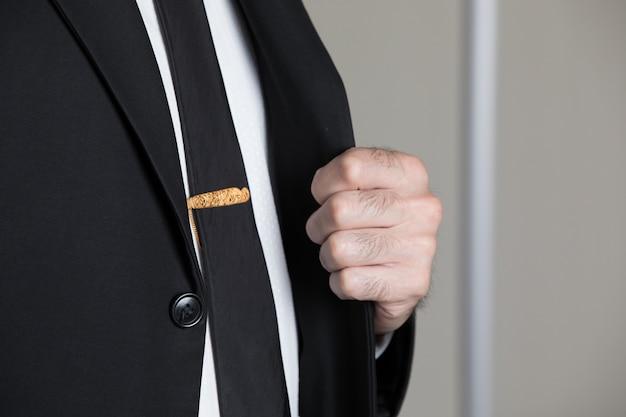 Alfinete dourado na gravata de um homem