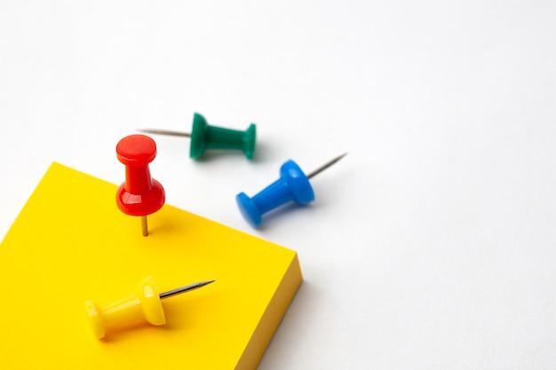Alfinete e papel de nota amarelo