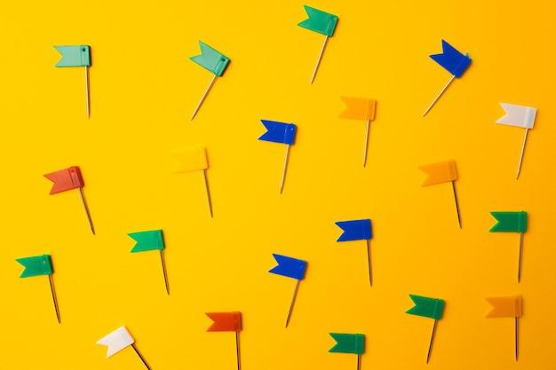 Alfinetes coloridos, padrão de clipes em fundo amarelo