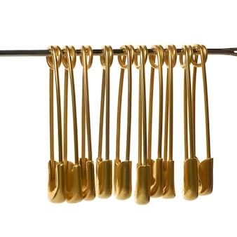 Alfinetes de segurança dourados isolados no branco
