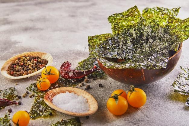 Alga nori crocante com tomate cereja e especiarias em uma tigela de madeira em concreto cinza. nori de comida japonesa. folhas secas de algas marinhas