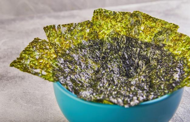 Alga nori friável em uma tigela azul sobre um fundo cinza. nori de comida japonesa. folhas secas de algas marinhas.
