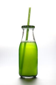 Algas orgânicas chlorella dissolvidas em água em uma garrafa transparente com um canudo em um fundo branco.