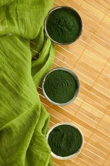 Algas spirulina, pó de spirulina e lenço verde na esteira de bambu