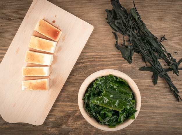 Algas wakame secas em fundo de madeira natural. alimentos saudáveis de algas com molho de soja e vista superior de tofu