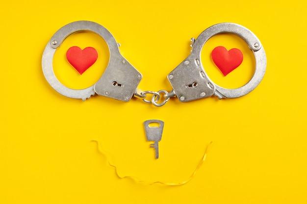 Algemas sorriem forma em fundo amarelo. conceito de liberdade. prisão, privação de liberdade e apreensão de agressores.