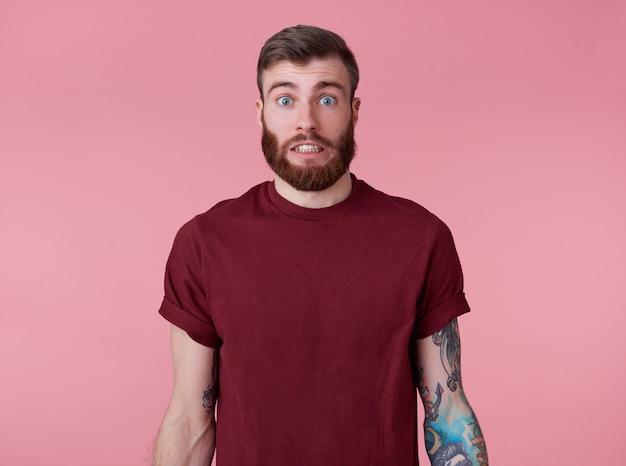 Algo errado! jovem atraente tatuado vermelho barbudo homem em t-shirt em branco, parece chocado e triste, fica sobre um fundo rosa.