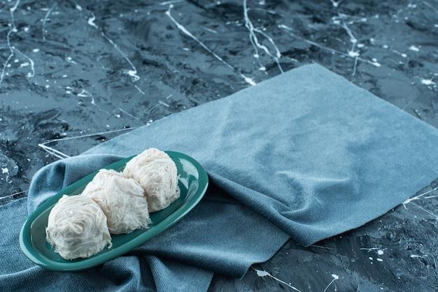 Algodão doce turco tradicional num prato sobre uma toalha, na mesa azul.