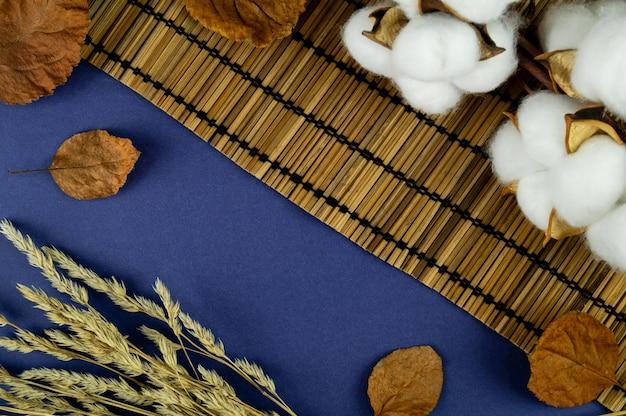 Algodão natural em cima da mesa com folhas. plano de fundo para seu objeto
