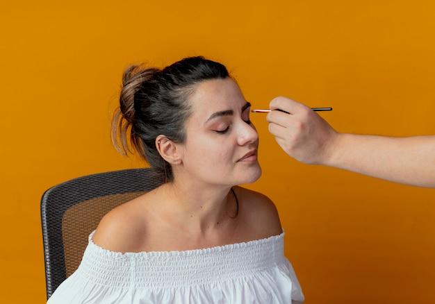 Alguém aplicando sombra com pincel de maquiagem nos olhos de uma linda garota sentada à mesa com ferramentas de maquiagem isoladas na parede laranja