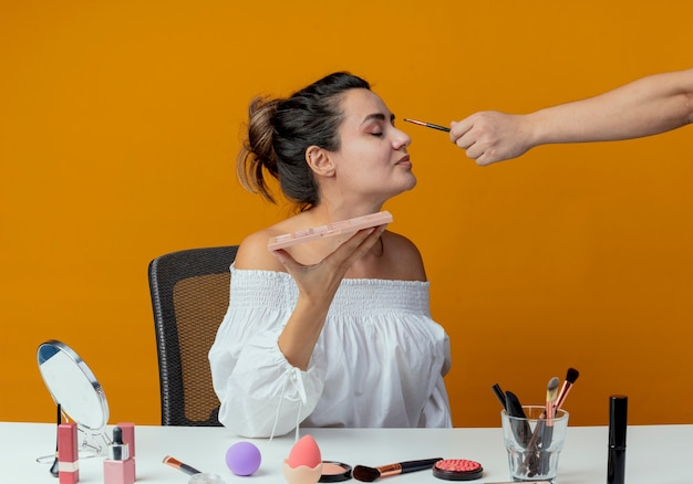Alguém aplicando sombra com pincel de maquiagem nos olhos de uma linda garota sentada à mesa com ferramentas de maquiagem segurando uma paleta de sombra isolada na parede laranja