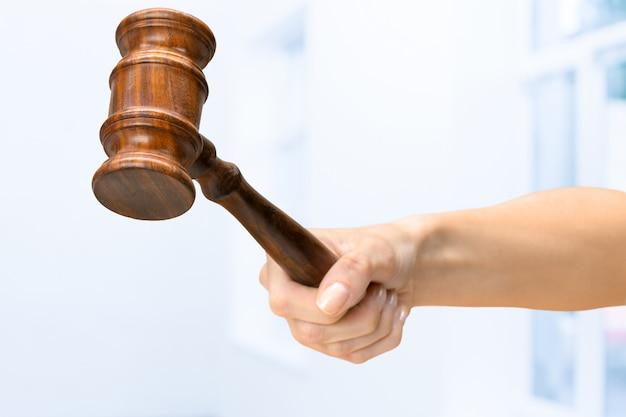 Alguém mão segurando o martelo de lei de madeira