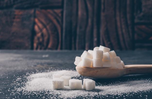 Algum açúcar branco em uma colher, vista lateral.