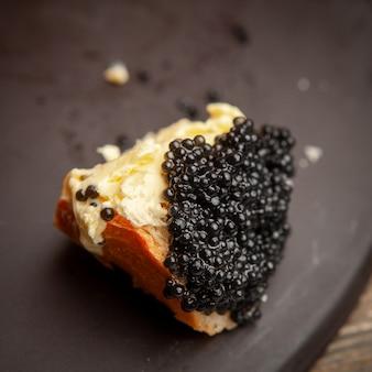 Algum caviar preto com manteiga no pão no fundo escuro, opinião de ângulo alto.