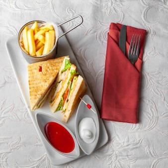 Algum fast food com sanduíche, batatas fritas, forquilha e faca no fundo textured branco, vista superior.