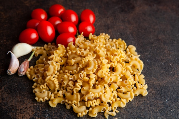 Algum macarrão com tomates e alho no fundo textured escuro, opinião de ângulo alto.