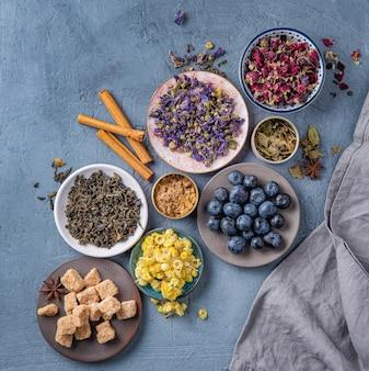 Algum prato com chá de ervas aromáticas camomila, lavanda e rosa, açúcar e mirtilos soltos na mesa azul