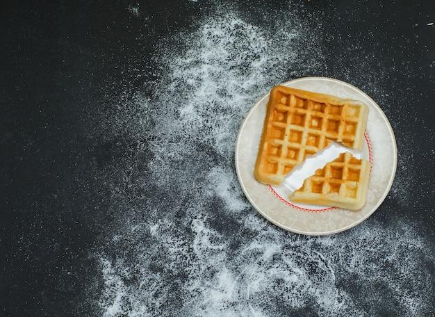 Algum waffle quebrado em um prato na vista superior escura.