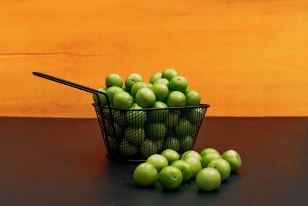Alguma ameixa de cereja verde com diversas ameixa de cereja verde em torno dele em uma bacia preta do ferro no fundo alaranjado, opinião de ângulo alto.
