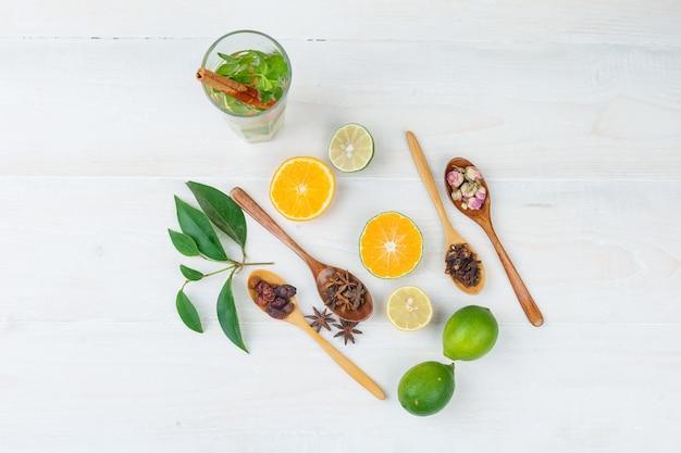 Alguma bebida fermentada com frutas cítricas, cravo e frutas secas na superfície branca