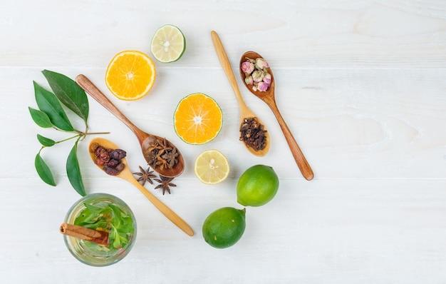 Alguma bebida fermentada com frutas cítricas, ervas e especiarias na superfície branca