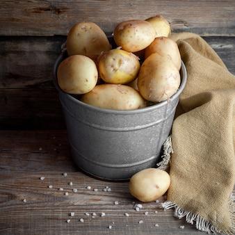 Algumas batatas em um balde cinza no fundo escuro de madeira, vista de alto ângulo.