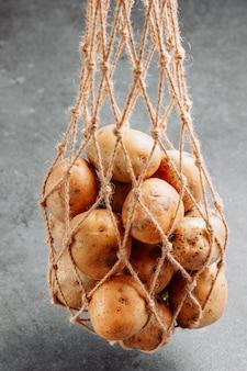 Algumas batatas em um saco líquido no fundo texturizado escuro, vista lateral.