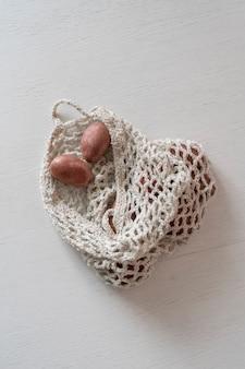 Algumas batatas vermelhas cruas em um tecido de malha implorando plano, vista de cima
