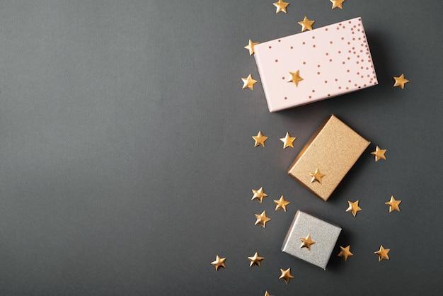 Algumas caixas de presente com estrelinhas douradas sobre a mesa preta, dia dos namorados ou conceito de dia de nascimento