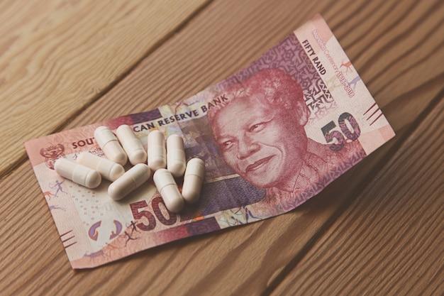 Algumas cápsulas em um sul-africano de 50 rands em uma mesa de madeira