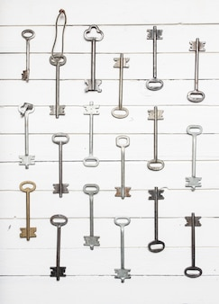 Algumas chaves da porta alinhadas no antigo fundo de conceito de superfície, segurança e segurança de madeira.