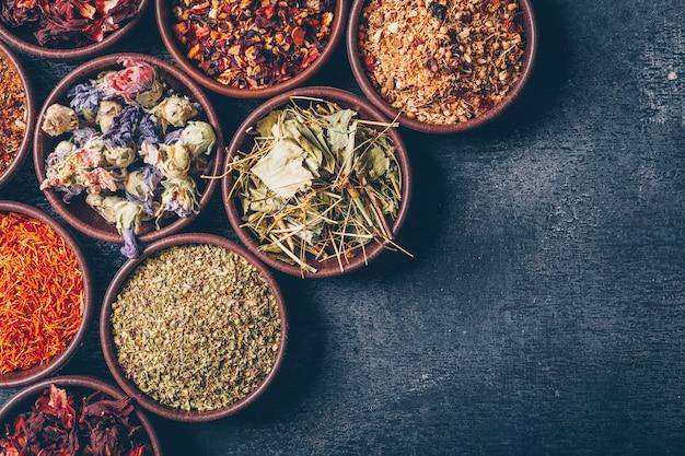 Algumas ervas de chá no tigelas no fundo escuro texturizado, vista superior. espaço para texto