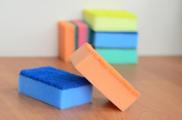 Algumas esponjas de cozinha encontram-se em uma bancada de cozinha de madeira