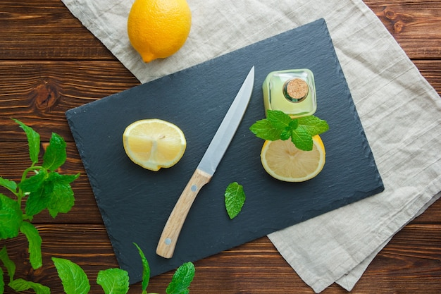 Algumas fatias de limão com papelão preto, garrafa de suco, faca de madeira em uma tigela na superfície de madeira, vista superior.