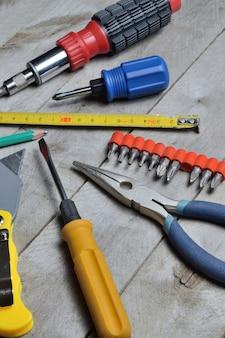 Algumas ferramentas de reparo doméstico encontram-se em um fundo de madeira. fechar-se.