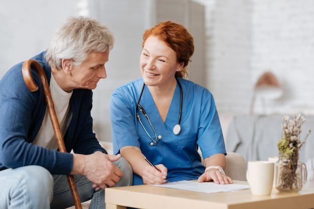 Algumas formalidades. excelente profissional médico experiente, contando ao paciente sobre os serviços que ela oferece, enquanto ele deseja contratá-la para cuidar dele