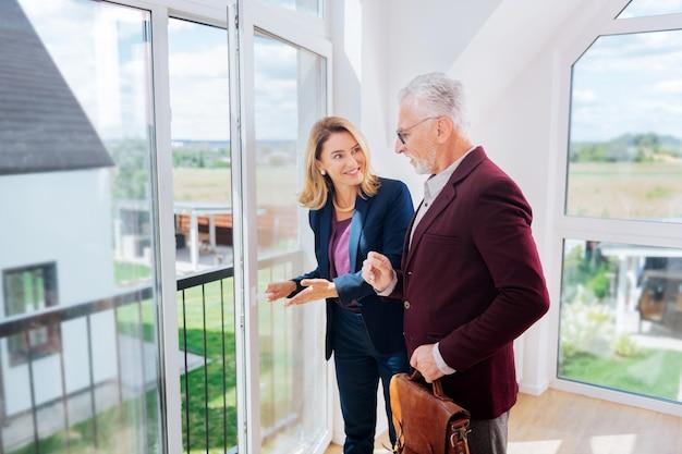 Algumas hesitações. homem de negócios barbudo vestindo uma jaqueta elegante e hesitando em comprar uma casa nova perto de uma corretora de imóveis