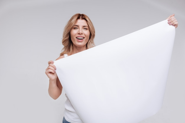 Algumas informações úteis. mulher jovem e radiante segurando uma grande folha de papel em branco enquanto sorri