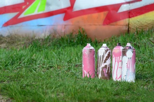 Algumas latas de tinta usadas ficam no chão, perto da parede, com uma bela pintura de grafite. arte de rua e vandalismo