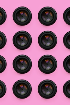 Algumas lentes de câmera com uma abertura fechada encontram-se no fundo da textura da cor pastel cor-de-rosa da forma